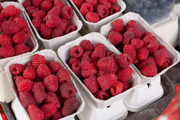 Fresh organic raspberries at farmers market in city