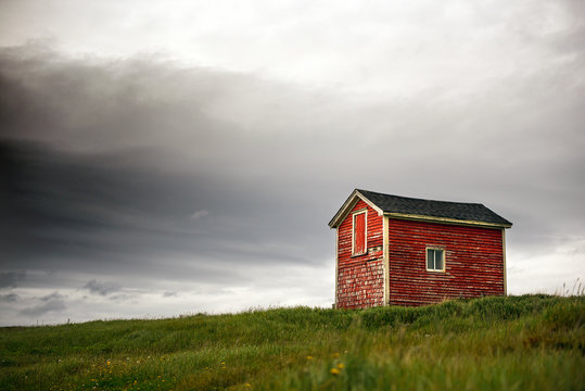 Tiny red building in green grass with dark clouds