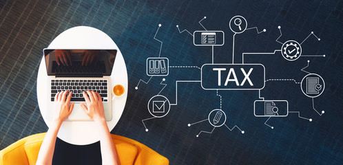 Wall Mural - Tax theme with person using a laptop on a white table