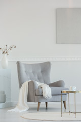 White blanket on grey armchair next to coffee table in bright living room