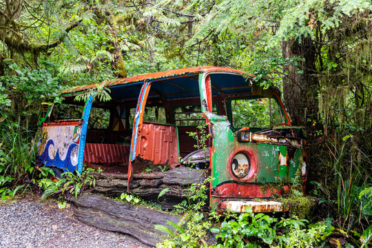 Abandoned camper van with psychedelic paint work photographed in a forest in British Columbia, Canada