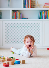 cute toddler baby boy playing with wooden blocks on the carpet