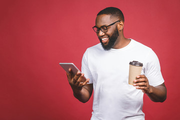 Typing a message. Cheerful black man typing something on the mobile phone, drinking coffee and smiling while standing isolated against red background. Fototapete
