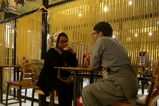 A couple sits for dinner at a shop called A Burger, in Kabul,