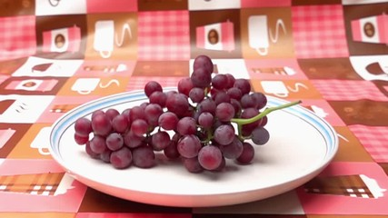 Fototapete - Bunch of ripe seedless grapes falls into a white plate in Slow Motion
