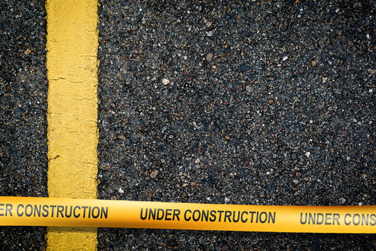 Asphalt with yellow road line with underconstruction warning tape.