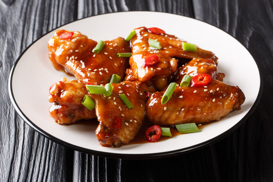 Recipe for delicious baked chicken wings with teriyaki sauce close-up on a plate. horizontal