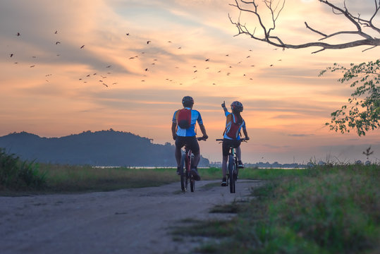 couple lover biker cyclist riding enjoyment to the field of meadow lake at sunset, adventure bicycle wild and journey activity.