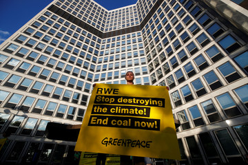 A Greenpeace activist holds a sign while protesting against climate change in front of the headquarters of German utility RWE in Essen