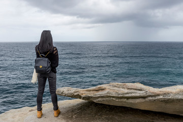 Young woman standing on a cliff watching the rough sea on a bad weather day