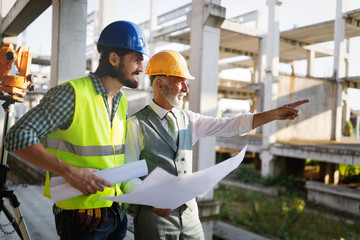 Obraz Team of business people in group, architect and engeneer on building site check documents - fototapety do salonu