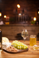 Cheese platter with fresh grapes and glasses of white wine on a rustic wooden table in a vintage pub.