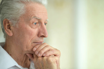 Beautiful sad thinking senior man posing at home