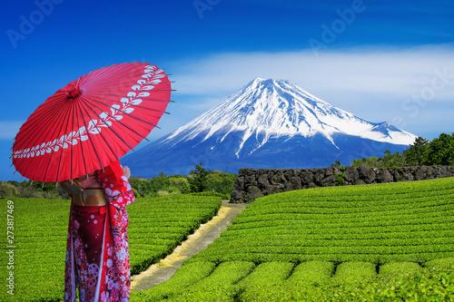 Wall mural Asian woman wearing japanese traditional kimono at Fuji mountains and green tea plantation in Shizuoka, Japan.