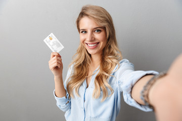 Photo of lovely blond businesswoman smiling and holding credit card while taking selfie