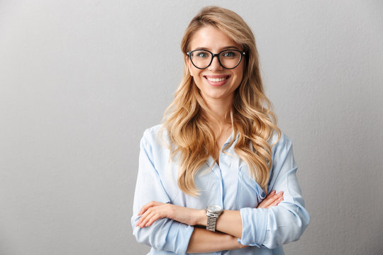 Photo of happy blond businesswoman wearing eyeglasses smiling and standing with hands crossed