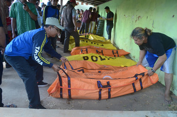 Men arrange body bags containing victims from the boat that sank in the sea between Sapudi and Gili islands, East Java province