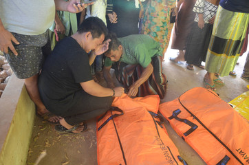 A relative of a passenger of a boat that sank in the sea between Sapudi and Gili islands cries as he checks a body bag at Dungkek district in Sumenep, East Java province
