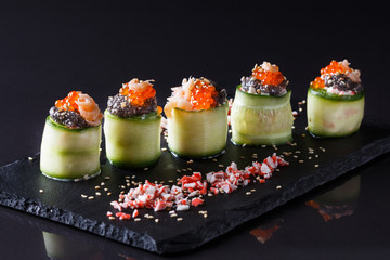 rolls covered in cucumber with caviar and prawn