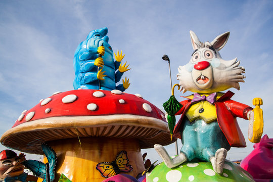 A caterpillar Absolem and white rabbit sitting on mushroom giant sculpture from Alice in wonderland on a carnival parade