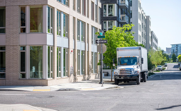 Compact rig semi truck with box trailer for moving and local delivery standing on the city street for loading goods