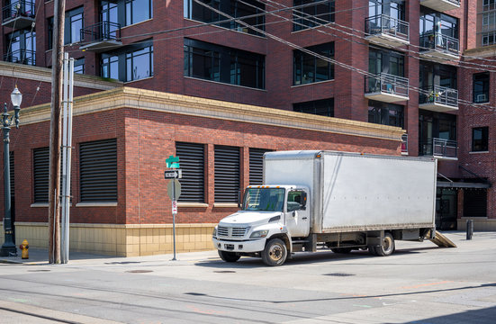 Compact small rid semi truck with box trailer standing in down town for loading moving goods