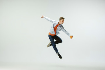 Happy young man working at office, jumping and dancing in casual clothes or suit isolated on white...