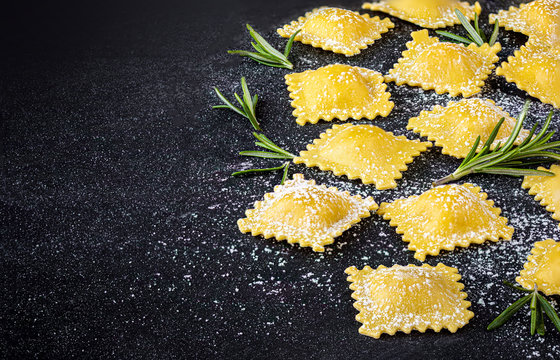 Fresh ravioli pasta  on dark background, top view.  Italian Raviolli close up. Copy space.