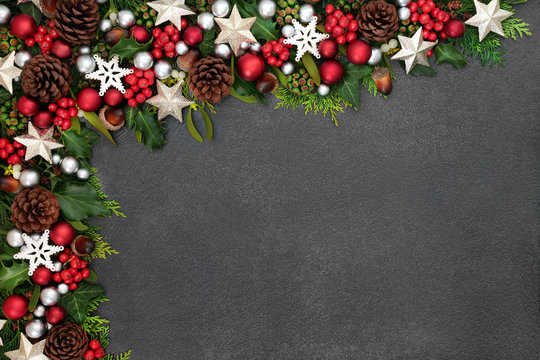 Festive Christmas background border with star and ball baubles, holly, mistletoe and winter flora on grunge grey background with copy space.