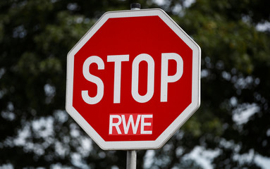 A stop sign is used to protest against German utility RWE with a sticker of the NGO Attac