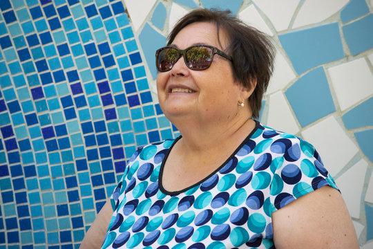 Señora mayor (abuela) mirando al cielo con una sonrisa y con gafas de sol y una camiseta azul en un parque con un mosaico de color azul en un día soleado de verano.