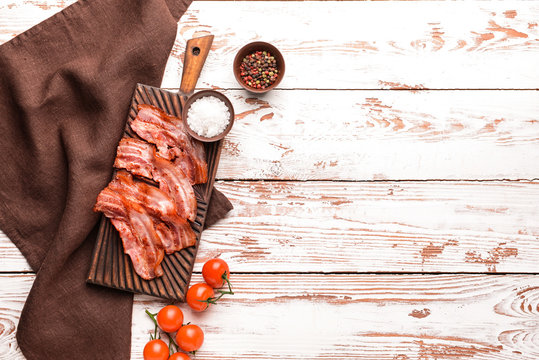 Fried bacon with spices on white table