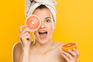 Portrait of young shirtles beautiful woman posing with grapefruit on yellow background