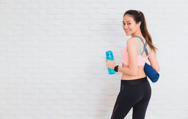 Asian beautiful women holding water bottle and yoga mat after play yoga and exercise on white brick wall background with copy space.Exercise for Lose weight,increase flexibility and tighten the shape.