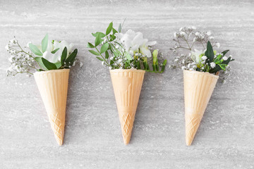 Wafer cones with beautiful freesia flowers on grey background