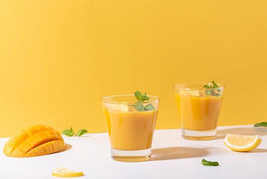 Fresh mango smoothie and ripe mango slice on color background. summer drink.