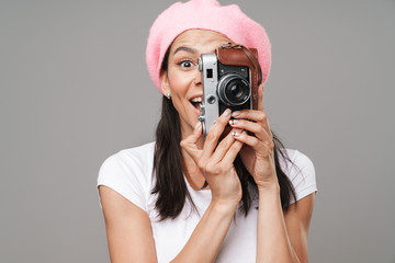 Image closeup of surprised young tourist woman in beret wondering and photographing on retro vintage camera
