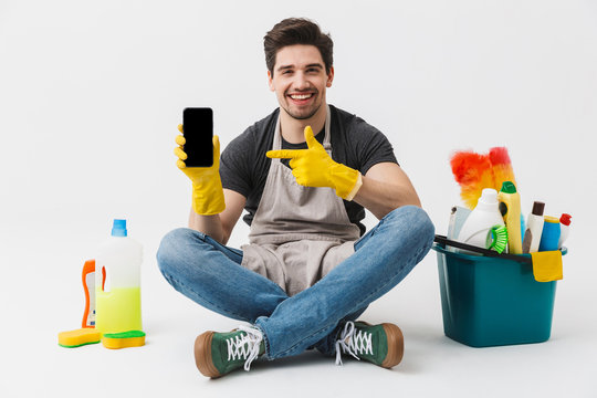 Happy excited young houseman househusband with cleansers on floor isolated over white wall background showing display of mobile phone.