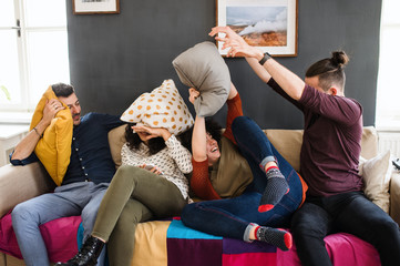 A group of young friends indoors at home, having fun. House sharing concept.