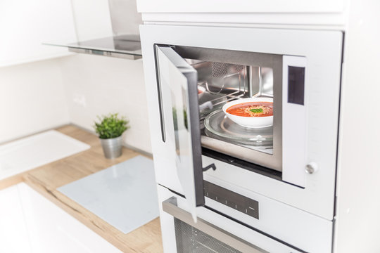 Built-in microwave oven  in the kitchen with tomato soup in white plate