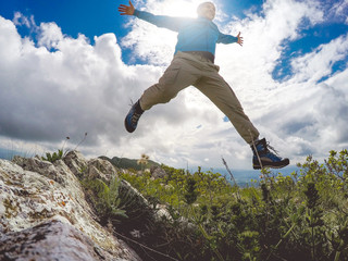 Male hiker jumping on a rocky mountain