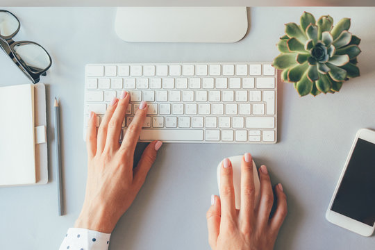 Top view of the workplace, elegant female hands on the keyboard of a personal computer in the office or at home, suitable for both freelancing and office content. Business lady prints