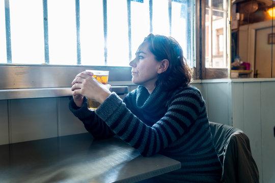 Alcoholic depressed woman drinking in a bar feeling sad hopeless