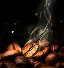 Photo sur Aluminium Salle de cafe Roasted coffee beans. Seeds of freshly roasted coffee with smoke. Coffee beans closeup with emphasis on the grain with smoke.