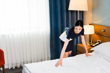 happy housemaid touching white bedding in hotel room