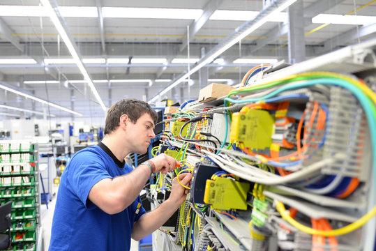 Montage im Maschinenbau durch jungen Arbeiter in einer modernen Fabrik // Assembly in mechanical engineering by young workers in a modern factory