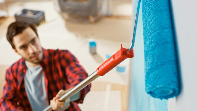 Close-Up Shot of a Man in Brown Jeans and Red Checked Shirt Painting a Wall with a Roller. Paint Color is Light Blue. Room Renovations at Home. Shot From Above.
