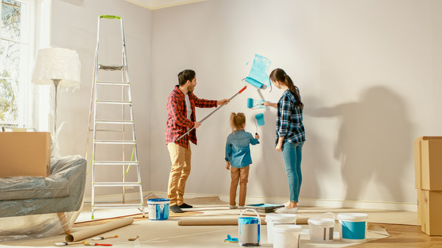 Beautiful Young Family are Showing How to Paint Walls to Their Adorable Small Daughter. They Paint with Rollers that are Covered in Light Blue Paint. Room Renovations at Home.