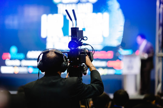 selective focus to cameraman and video camera set are recording to speaker and audience in conference hall or seminar event.