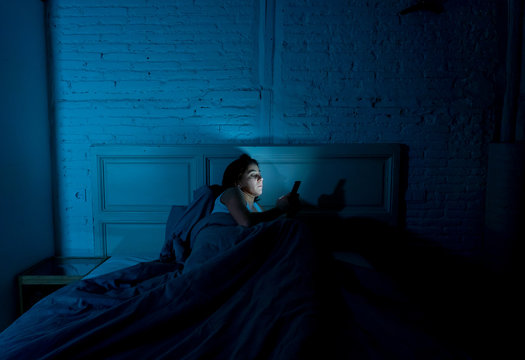 young beautiful woman lying bored in bed using smart phone late at night in a dark bedroom